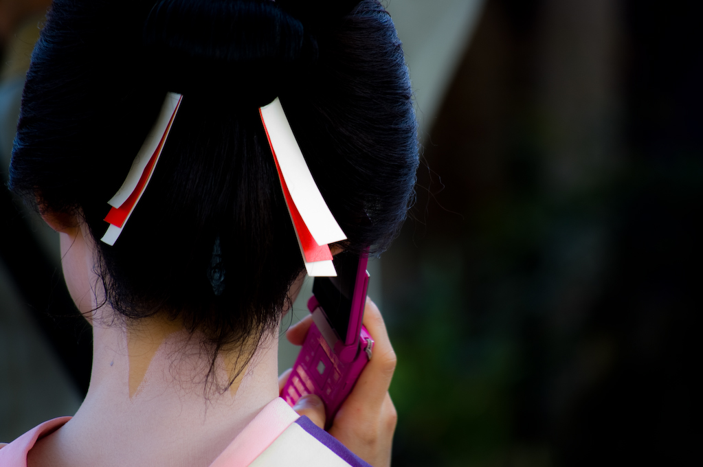 maiko with cellphone kyoto japan
