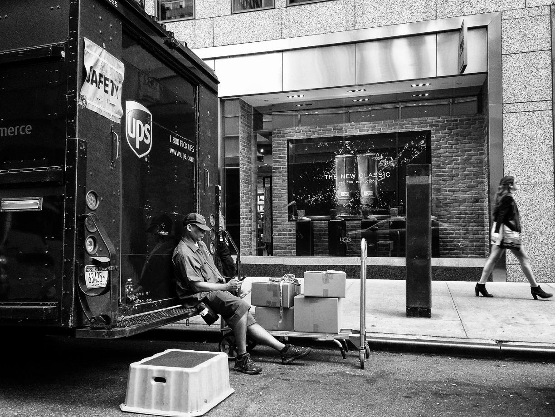 Repartidor descansando y mujer paseando – Nueva York